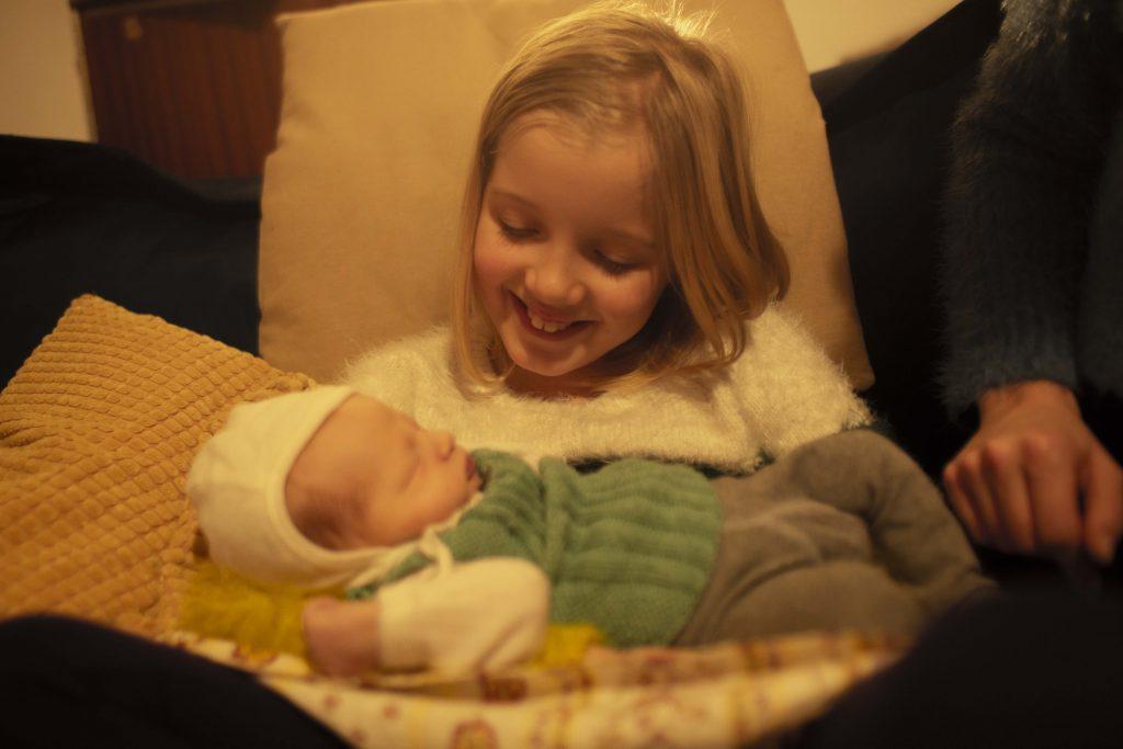 Pige holder nyfødt lillebror og smiler