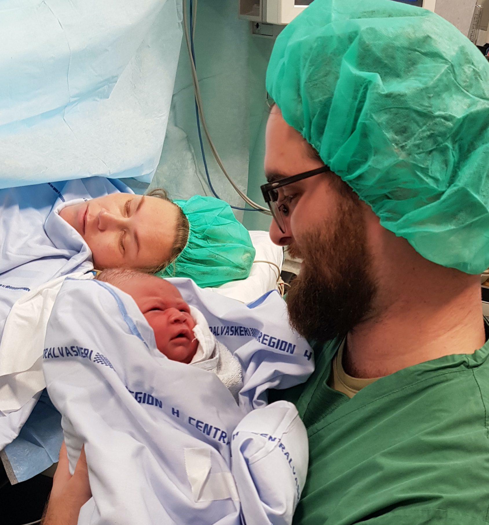 Vanessa ligger på hospitalsseng, nyfødt Hugo holdes af far