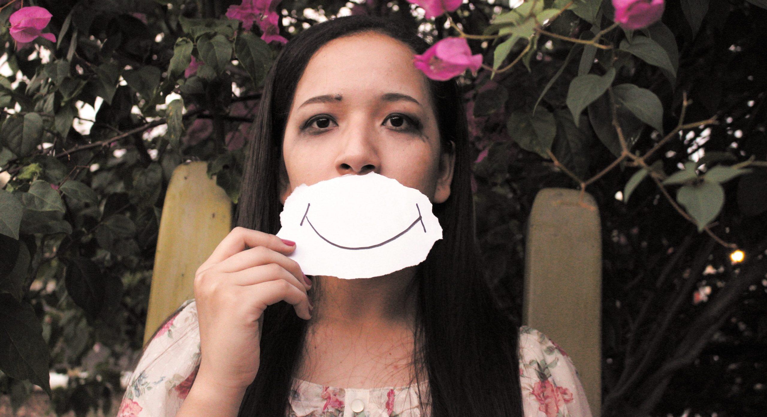 Kvinde holder tegning af et smil foran ansigtet